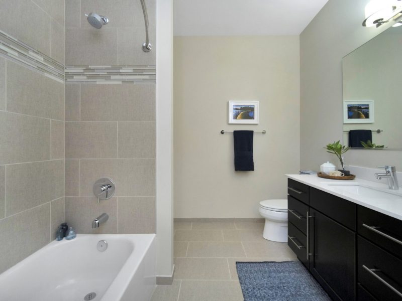 This image shows a contemporary bath that has quartz countertops, ceramic tile floors, and tub surrounds. It has an aisle directly passing to the kitchen area.