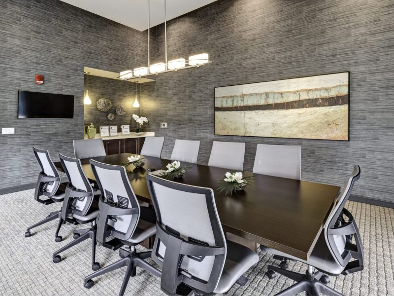 This image shows the door view of the conference room that features sophisticated chairs, tables, and lights.