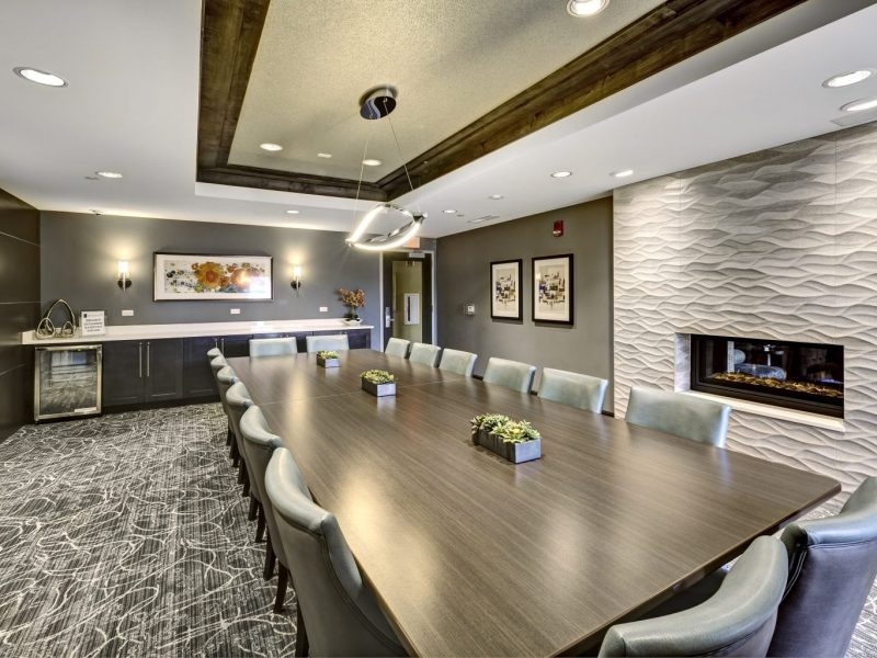 This image shows the conference room that features the sophisticated chairs, tables, and lights with a unique fireplace.
