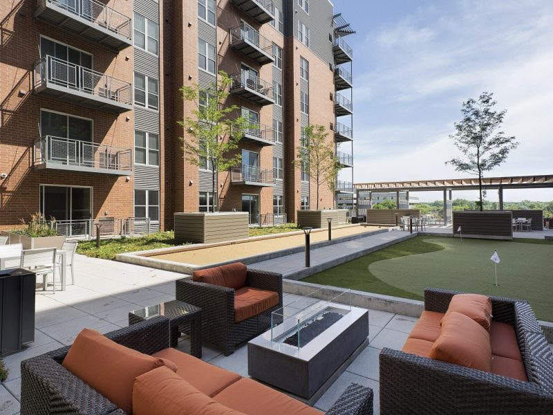 This image shows an expansive view of the Premium Community Amenities, specifically the outdoor fire pit, social lounge, community room, and a spacious putting green for a better fun experience.