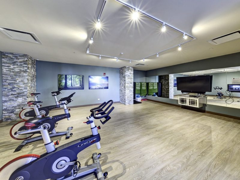 This image shows an expansive view of the fitness gym equipment featuring the yoga and spin studio with indoor cycling mirror that was ideal for flexibility and strength exercise.