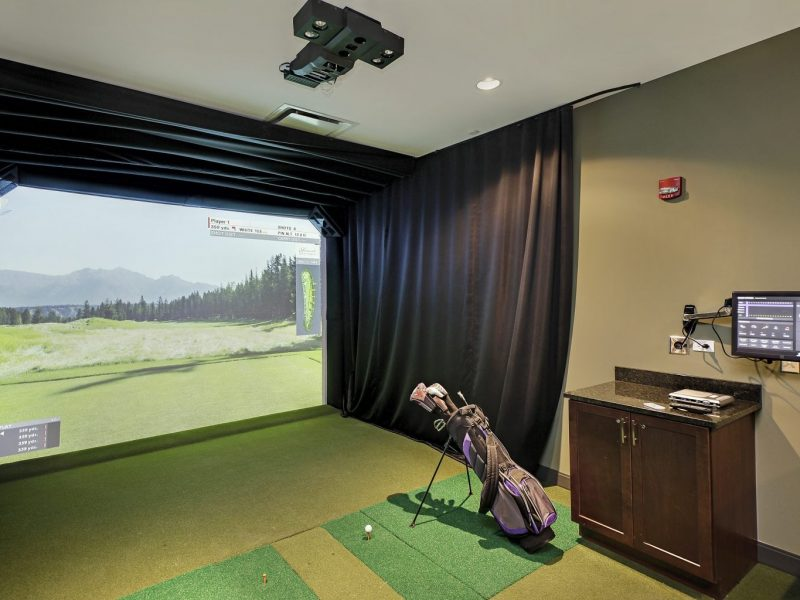 This image shows the indoor golf simulator or the umbrella term for all activities in golf that is visible indoor. Venues include indoor driving ranges, chipping areas, putting greens, and machines. Many of these indoor facilities are businesses that include additional entertainment options as well as food and drink for customers.