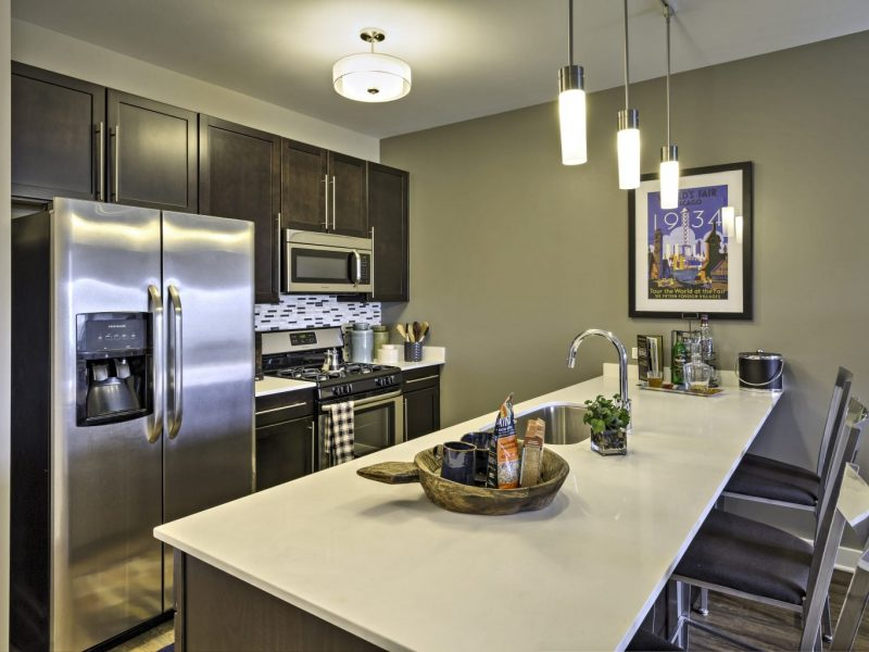This image shows a gourmet open kitchen with a breakfast bar and stunning lights. It features stainless steel appliances and built-in microwaves.