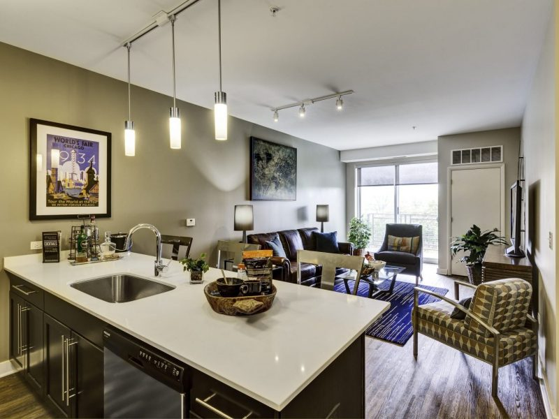 This image shows a gourmet open kitchen with a breakfast bar overviewing the living room area.