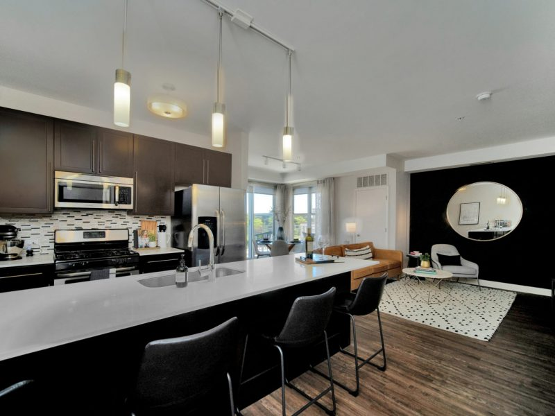This image shows the Premium Apartment Feature, especially the kitchen island showcasing a granite-inspired countertop, a neat design, stainless-steel appliances, and built-in microwaves.