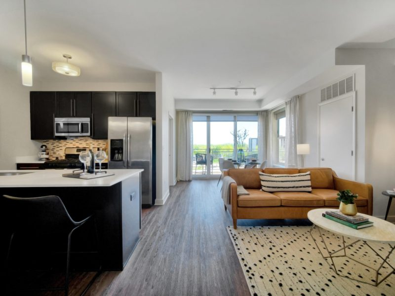 This image shows the living room area with modern floor mats and modern interior design that was accessible to the kitchen area and balcony.