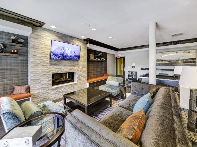 This image shows the resident lounge area with a flat-screen TV, fireplace, and comfortable pillows.
