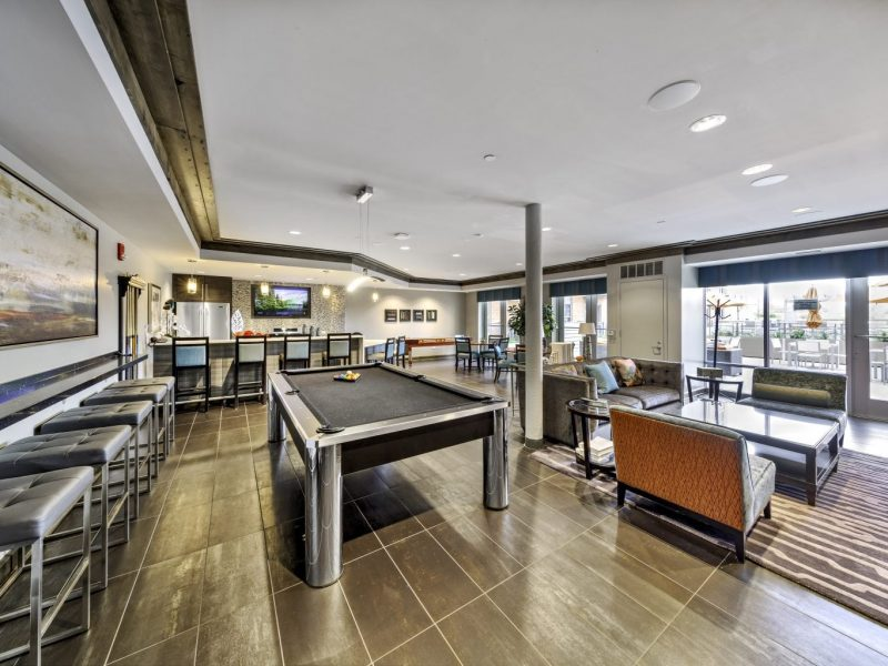 This image shows the social lounge with kitchen, billiard area, and seating.